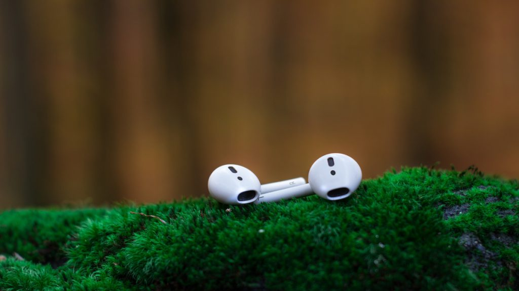 White AirPods on Green Surface.